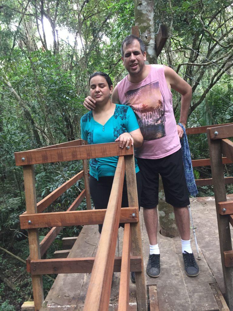 Atena e Marlon em pé na casinha da árvore com árvores e folhagens