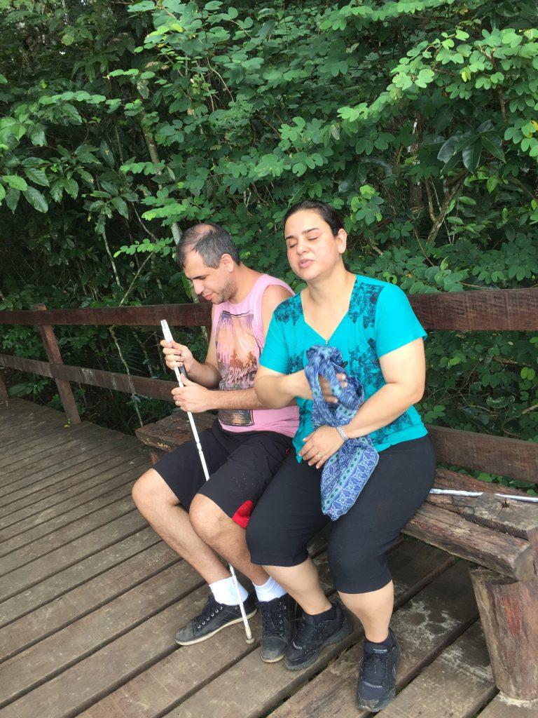 Atena e Marlon sentados no banquinho com folhagens