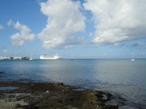 Praia com pedras e navio ao fundo